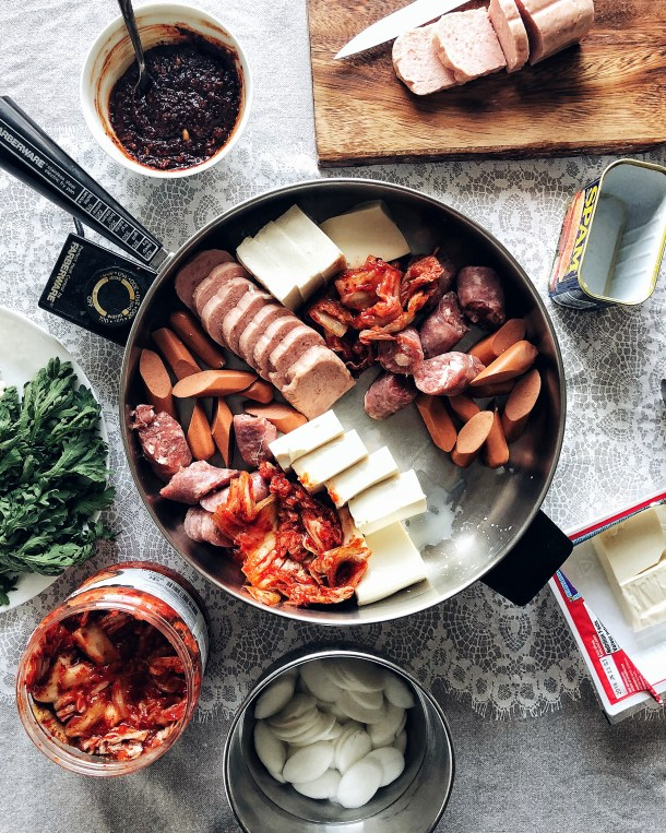 ingredients for budae jjigae in electric hot pot, surrounded by more ingredients