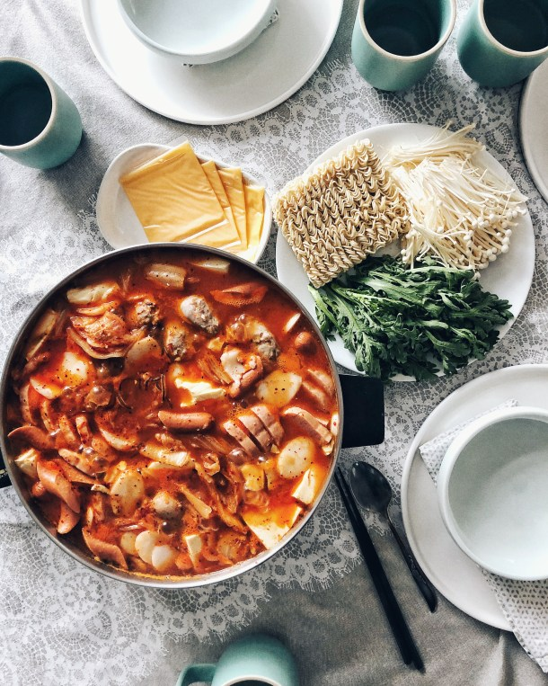 budae jjigae in electric hot pot with plate of ingredients nearby