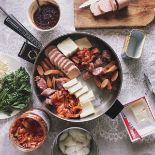 An insanely delicious one-pot wonder that fuses the best of two worlds. Spam, hot dogs, kimchi, instant noodles, and processed cheese slices combine into a simmering pot of spicy Korean deliciousness that is best eaten with others!