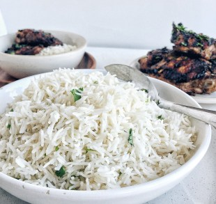 Coconut Rice in white bowl with grilled meat in background
