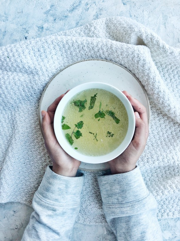 bowl of chicken broth with cilantro, held by two hands