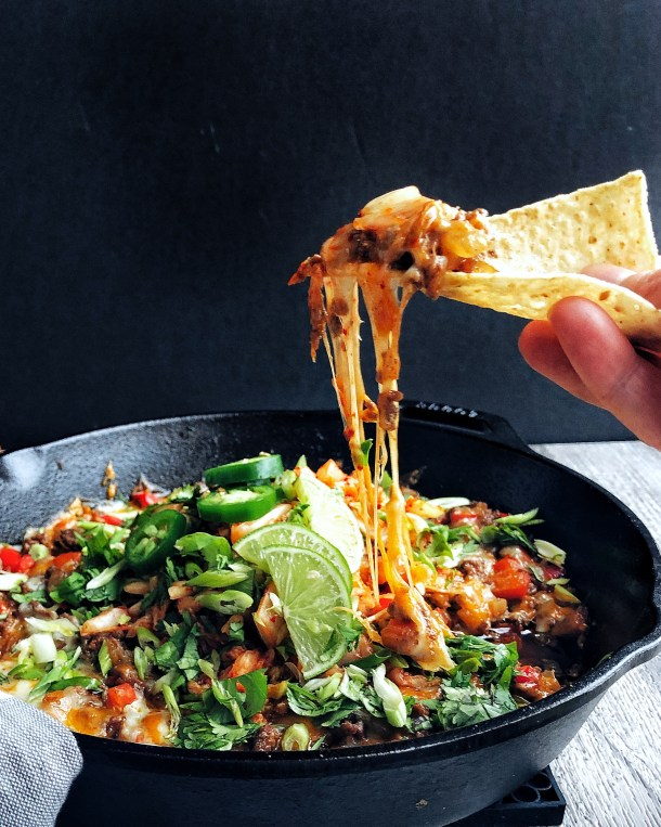 kimchi queso cheese dip in cast iron skillet and cheese pull