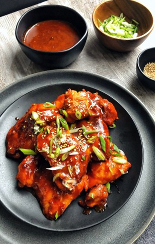 Gochujang Chicken on a plate with extra sauce on the side