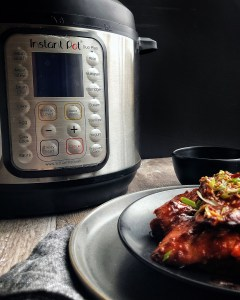 Instant Pot with plate of chicken in the corner