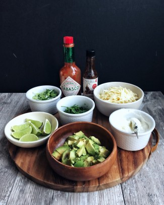 Chili toppings in bowls, on top of brown cutting board