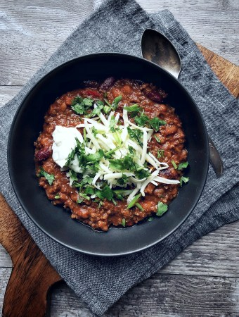 chili in bowl with cheese, cilantro, sour cream and grey napkin underneath