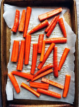 raw carrots on sheet pan with parchment paper