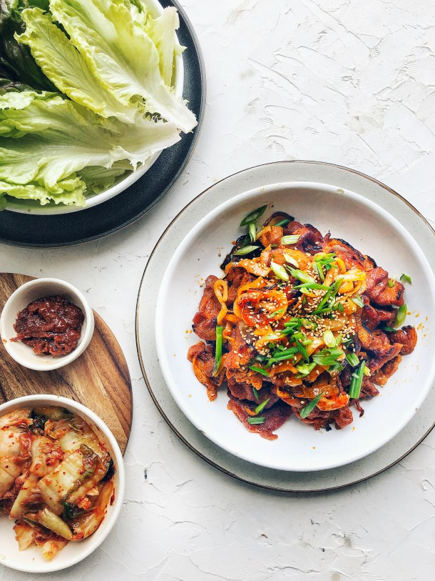 Spicy Korean Pork on a plate with lettuce wraps and kimchi on the side