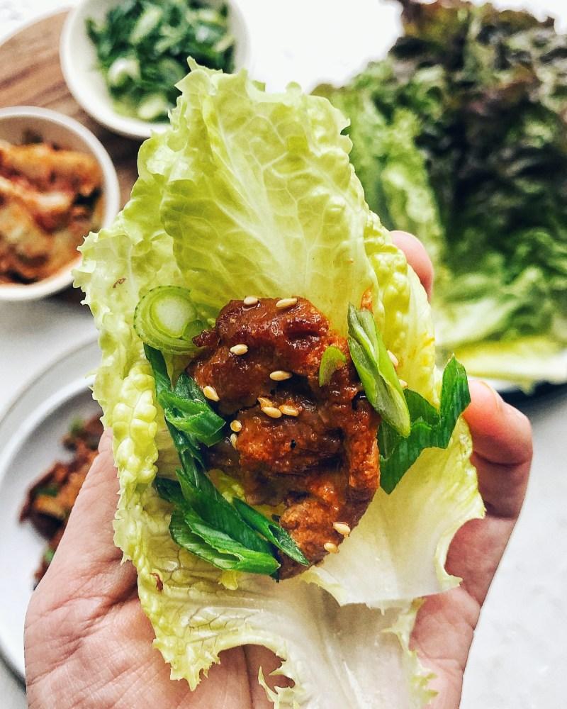 spicy korean pork in lettuce wrap, held by hand