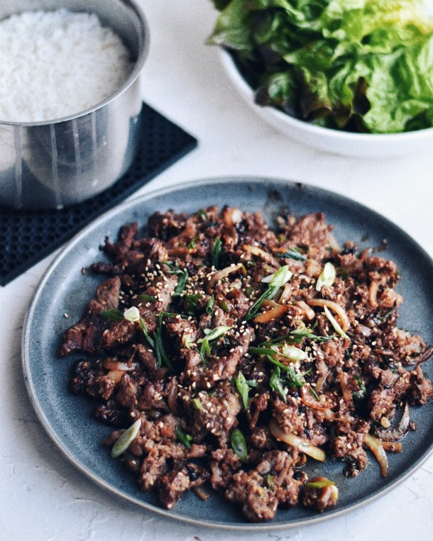 Korean beef bulgogi on a plate with rice and lettuce wraps on the side