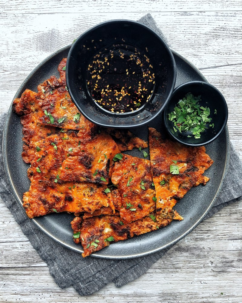 kimchi pancake on a plate with dipping sauce