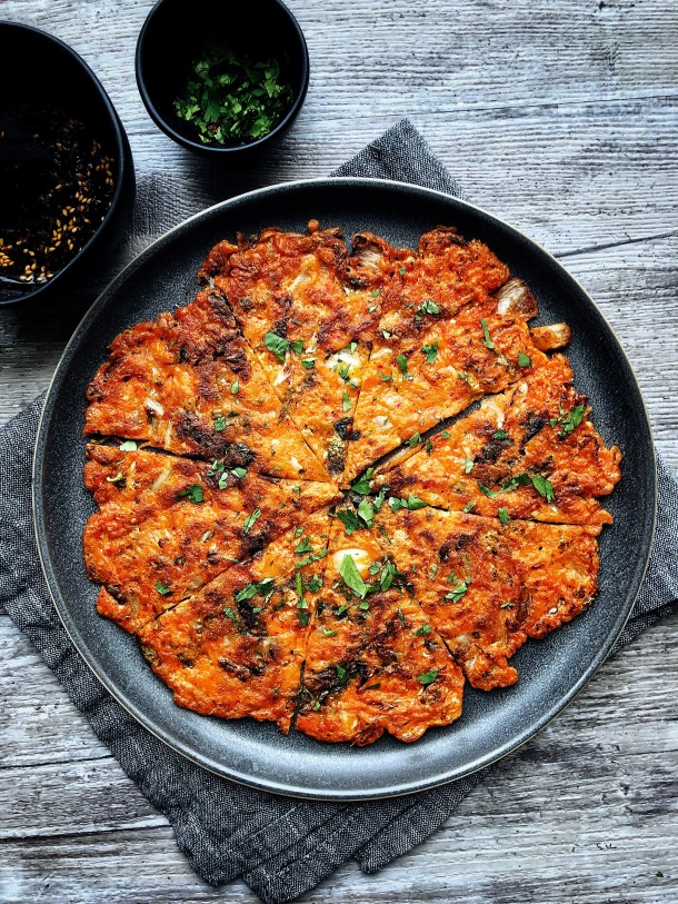 kimchi pancake on a plate, cut into pieces