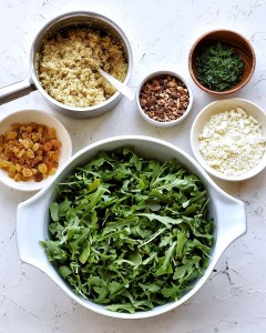 ingredients for arugula quinoa salad in separate bowls