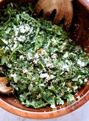 arugula quinoa salad in wooden bowl