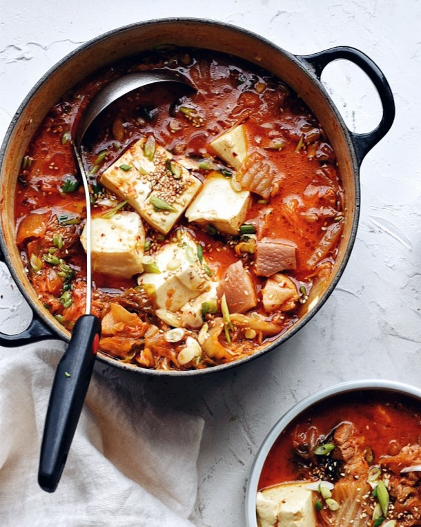 pot of kimchi stew and ladle next to a bowl of kimchi stew