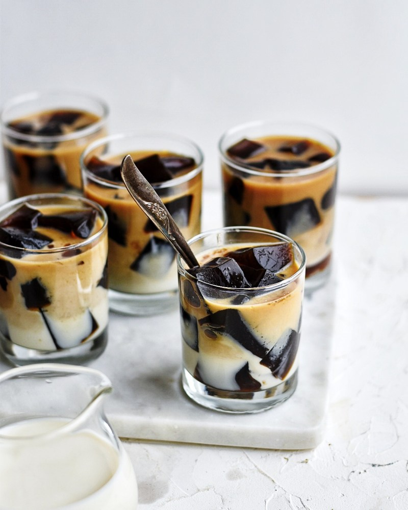 multiple glasses of coffee jello and sweet milk on white marble board