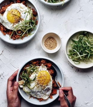 bowl of kimchi fried rice with fried egg in bowl and hands holding spoon and bowl