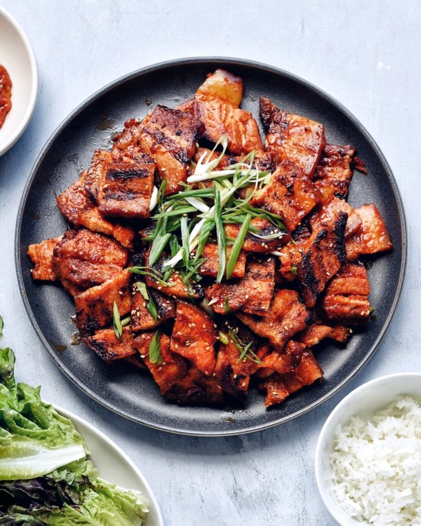 spicy pork belly bulgogi on dark plate with rice bowl and lettuce on a plate