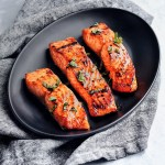 three asian glazed salmon fillets on black platter and grey napkin
