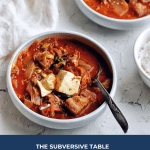 bowl of Kimchi stew with spoon with white napkin