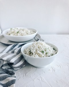 coconut rice in two white bowls with striped napkin