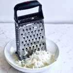 box grater in bowl with grated onion and asian pear