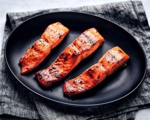 three asian glazed salmon fillets on black plate and grey napkin