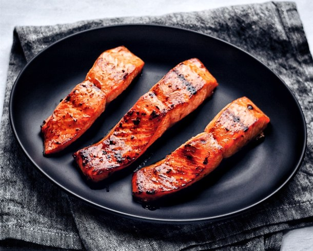 three asian glazed salmon fillets on black plate and grey napkin