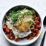 easy kimchi fried rice with fried egg and green onion garnish in bowl with spoon