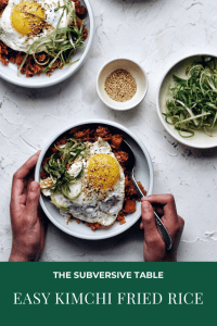 kimchi fried rice in bowl with fried egg on top and hands holding it