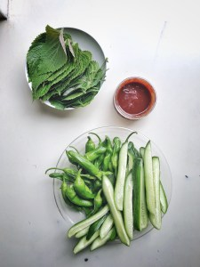 bowl of perilla leaves, bowl of cucumbers and peppers, and small bowl of gochujang sauce