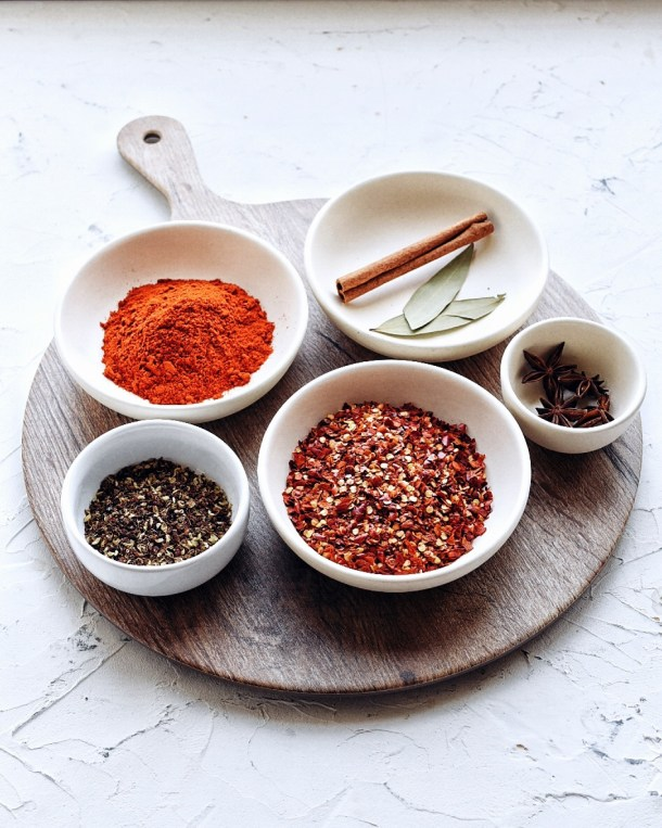 dry ingredients for chinese chili oil in separate bowl arranged on brown cutting board