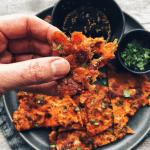 hand holding kimchi pancake with plate of kimchi pancakes behind