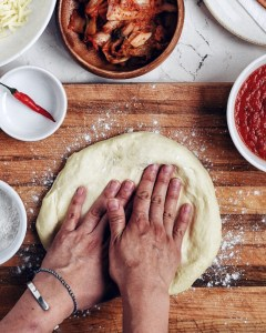 pizza dough on a cutting board with hands on top