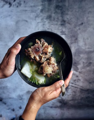 hands holding a bowl of korean oxtail soup