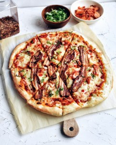 kimchi bacon pizza on parchment paper and round cutting board with ingredients in background