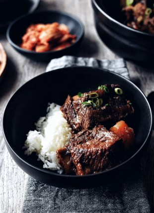 bowl of galbi jjim (Korean braised short ribs) with rice on grey napkin and wood table