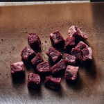 cubes of steak on cutting board