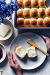 soft dinner rolls on a plate with hands