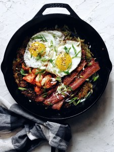 cast iron skillet filled with eggs, bacon, kimchi, hash browns