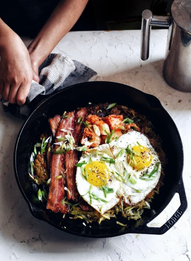 hands holding skillet full of egs, bacon, kimchi, hash browns