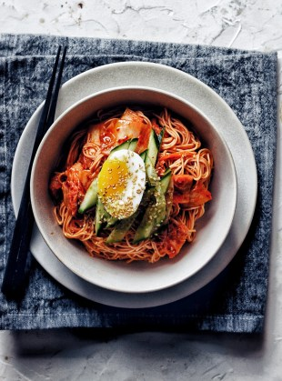 white bowl of bibim guksu on napkin with egg and cucumber