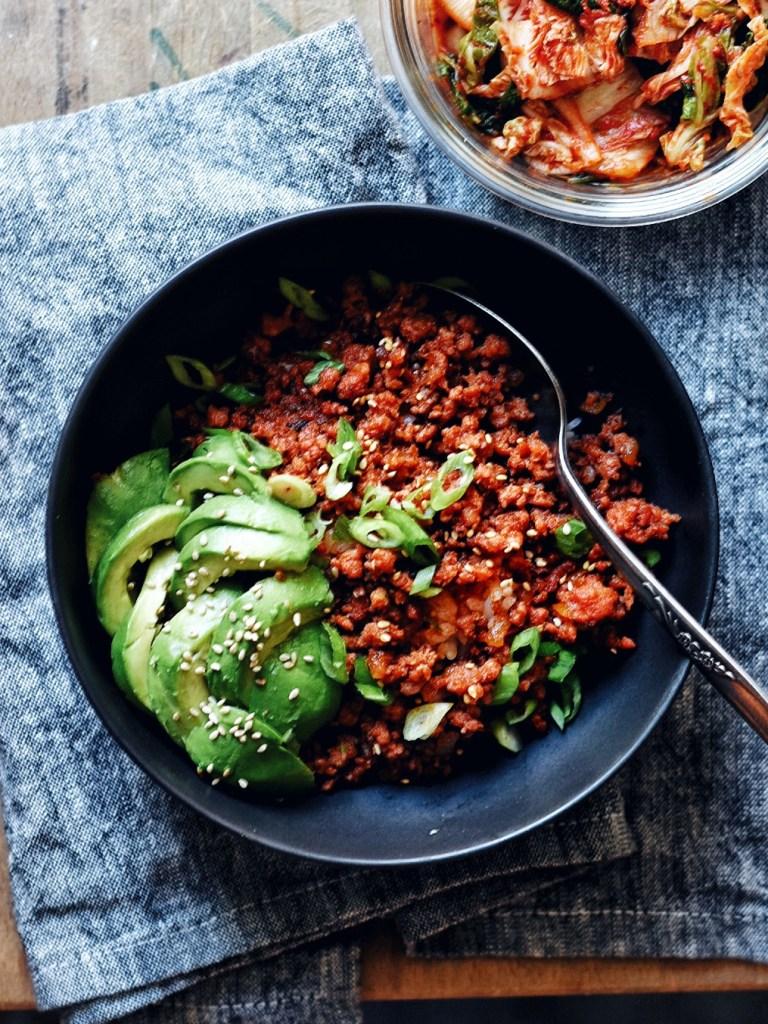 gochujang pork bowl with avocado and spoon on side