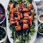 miso salmon skewers on oval platters with dishes on side
