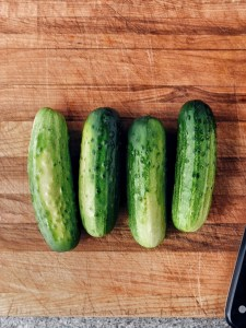 4 pickling cucumbers on brown cutting board