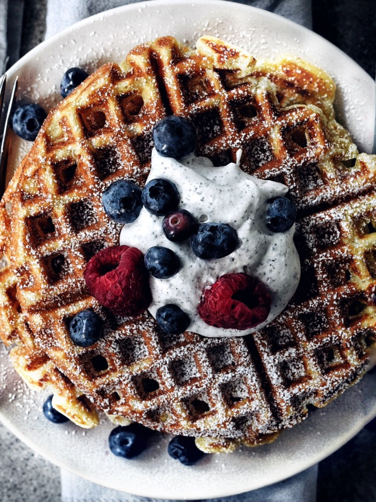close up of buttermilk waffles and black sesame whip with berries