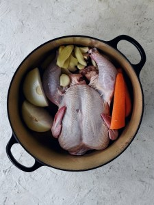 stock pot filled with whole chicken, carrot, onion, ginger, garlic