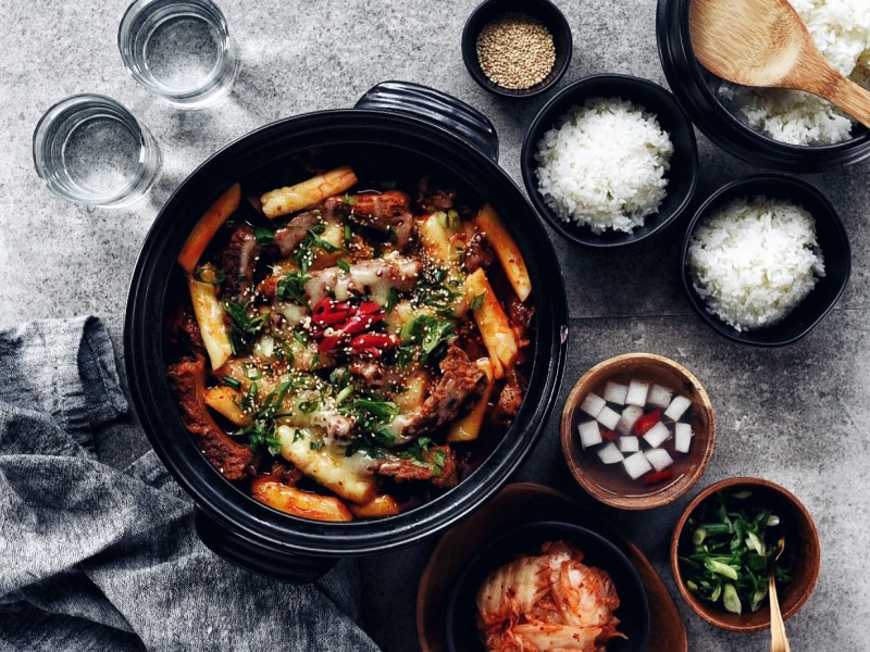 black shallow dish filled with spicy galbi jjim and little bowls of rice and banchan around it