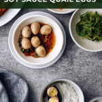 bowl of Korean soy sauce quail eggs next to other side dishes