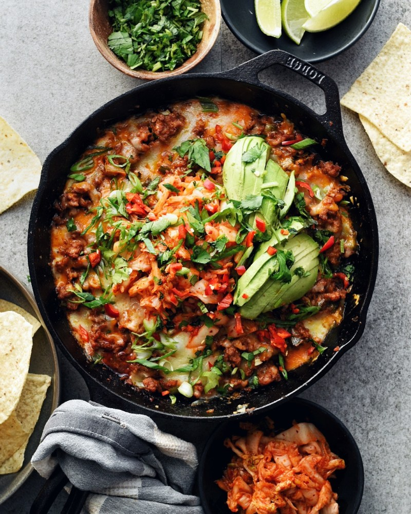 kimchi queso dip in cast iron pan with chips on the side